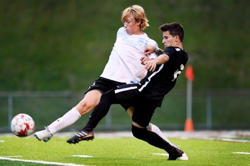 Enka's Eli Bonham kicks the ball away from Asheville's Andres Fraga Oct. 3, 2018 at Asheville High School.