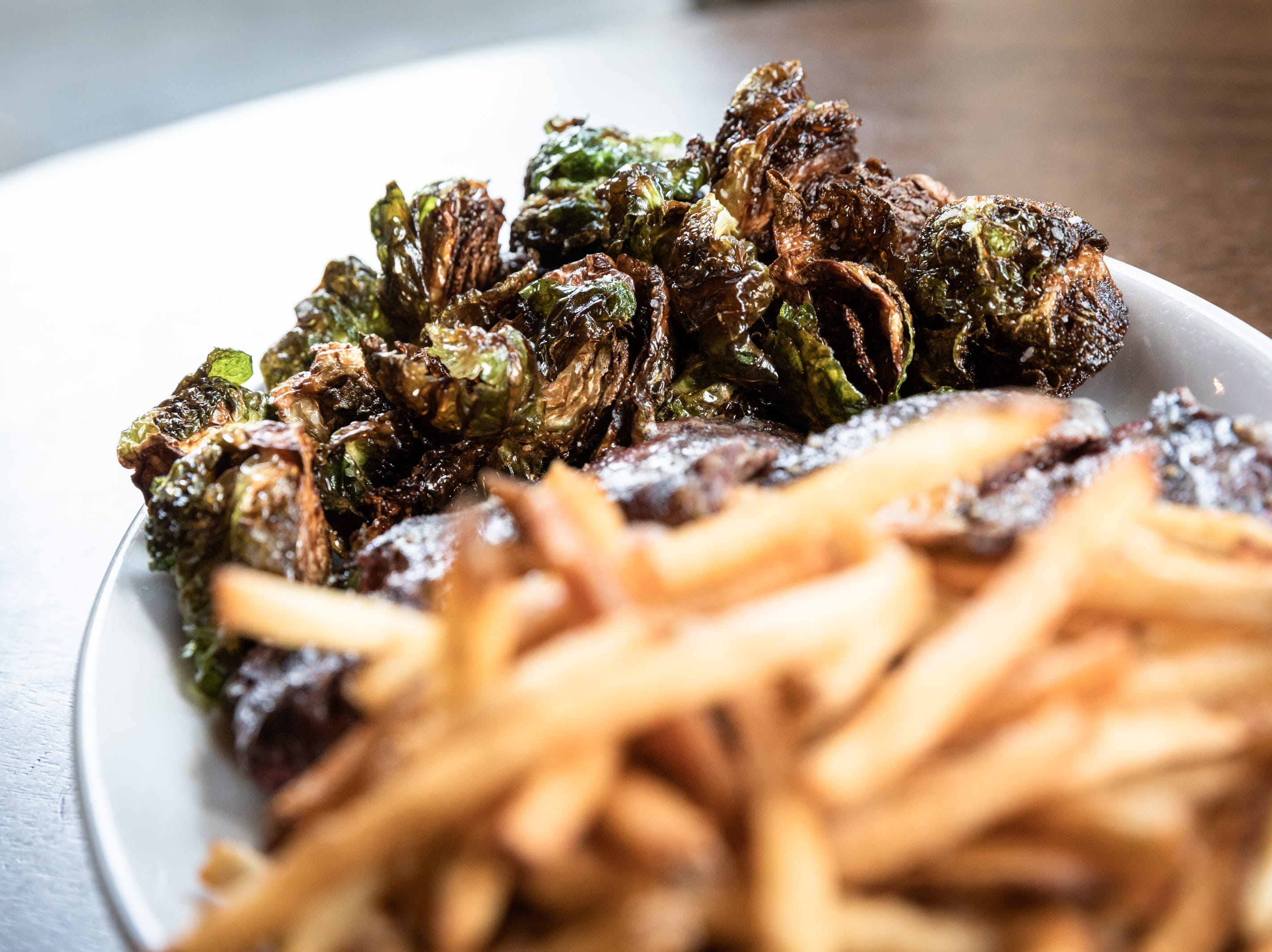 An 8 oz. Hereford Angus Dry-aged Denver steak from Apple Brandy Farms in Wilkesboro, with Brussels sprouts and frites, offered at Bone and Broth restaurant on Charlotte Street.