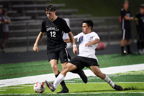 Enka's Kevin Blanco kicks the ball away from Asheville's Julian Pistor Asheville High School Oct. 3, 2018. Asheville won, 1-0.