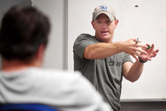 Rickey Brindley, Smoky Mountain's new football coach, talks to his team in the field house's weight room Oct. 2, 2018 in Sylva.