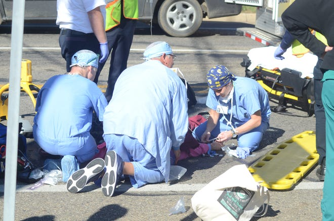 Emergency responders from Bronson Battle Creek Hospital treat a woman police say was struck by a pick-up truck which fled the scene on Thursday, Oct. 4, 2018.