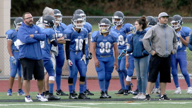 Olympic's junior varsity team, led by coach Keven Smith (right), played against Port Angeles with 21 players on Monday.