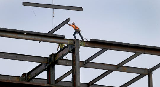 Workers move steel girders on the new nine-story tower complex under construction to expand the Harrison Medical Center in Silverdale on Sept. 10. The new hospital is scheduled to open in January 2020.