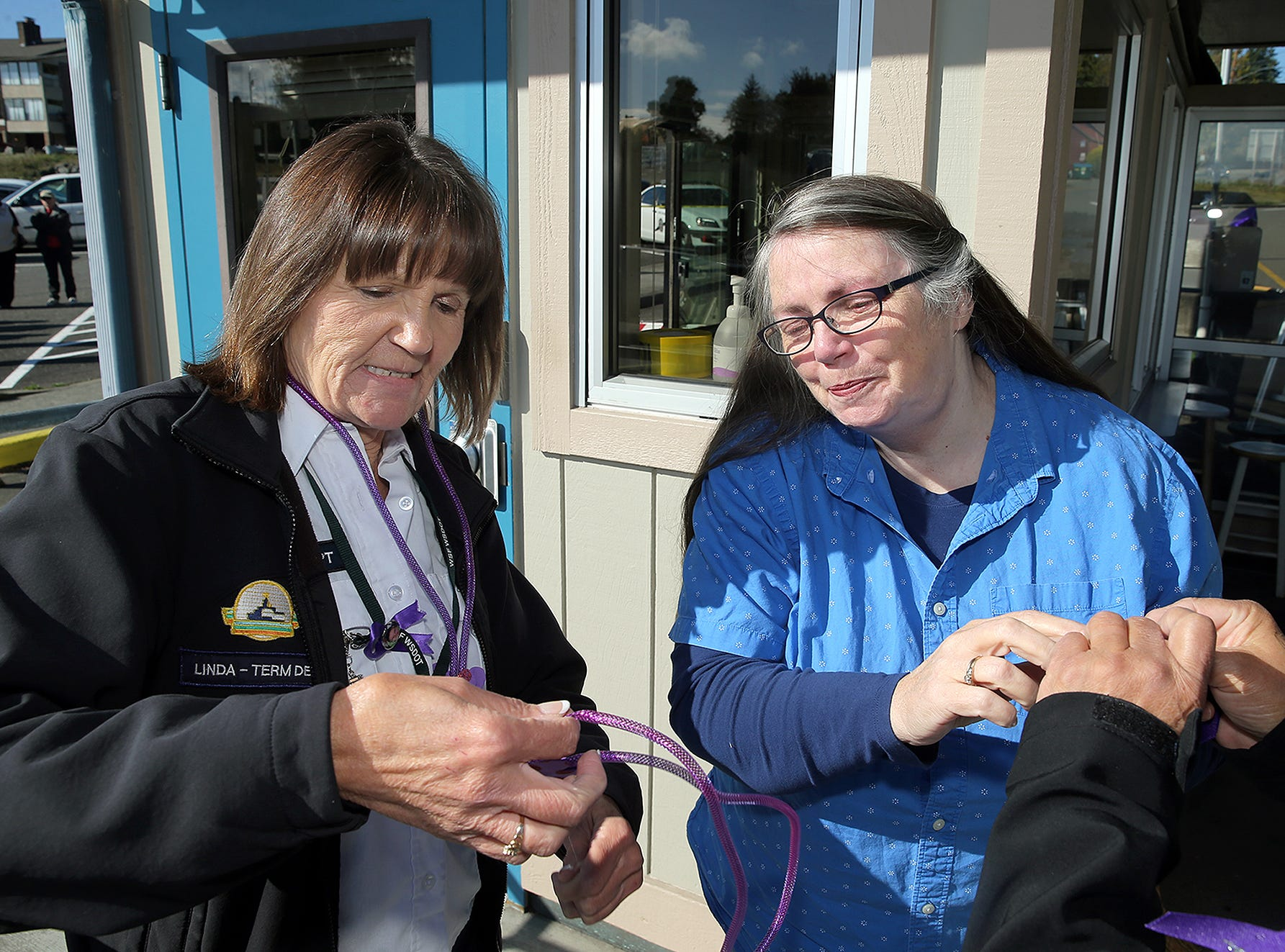 Deborah Harrah of Bremerton the mother of former Washington State Ferries employe Katie Phillips is given a purple necklace from her daughter's co-worker Linda Lindsley at the Southworth Ferry Terminal Thursday, October 4, 2018. Phillips passed away at a tragic accident on Highway 160 near Long Lake in Port Orchard. Southworth ferry workers and friends held a small memorial for Phillips outside the toll booths. Purple was Phillips favorite color.
