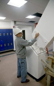 Maintenance foreman Lynn Cleary with one of the East Bremerton gymnasium's support beams.