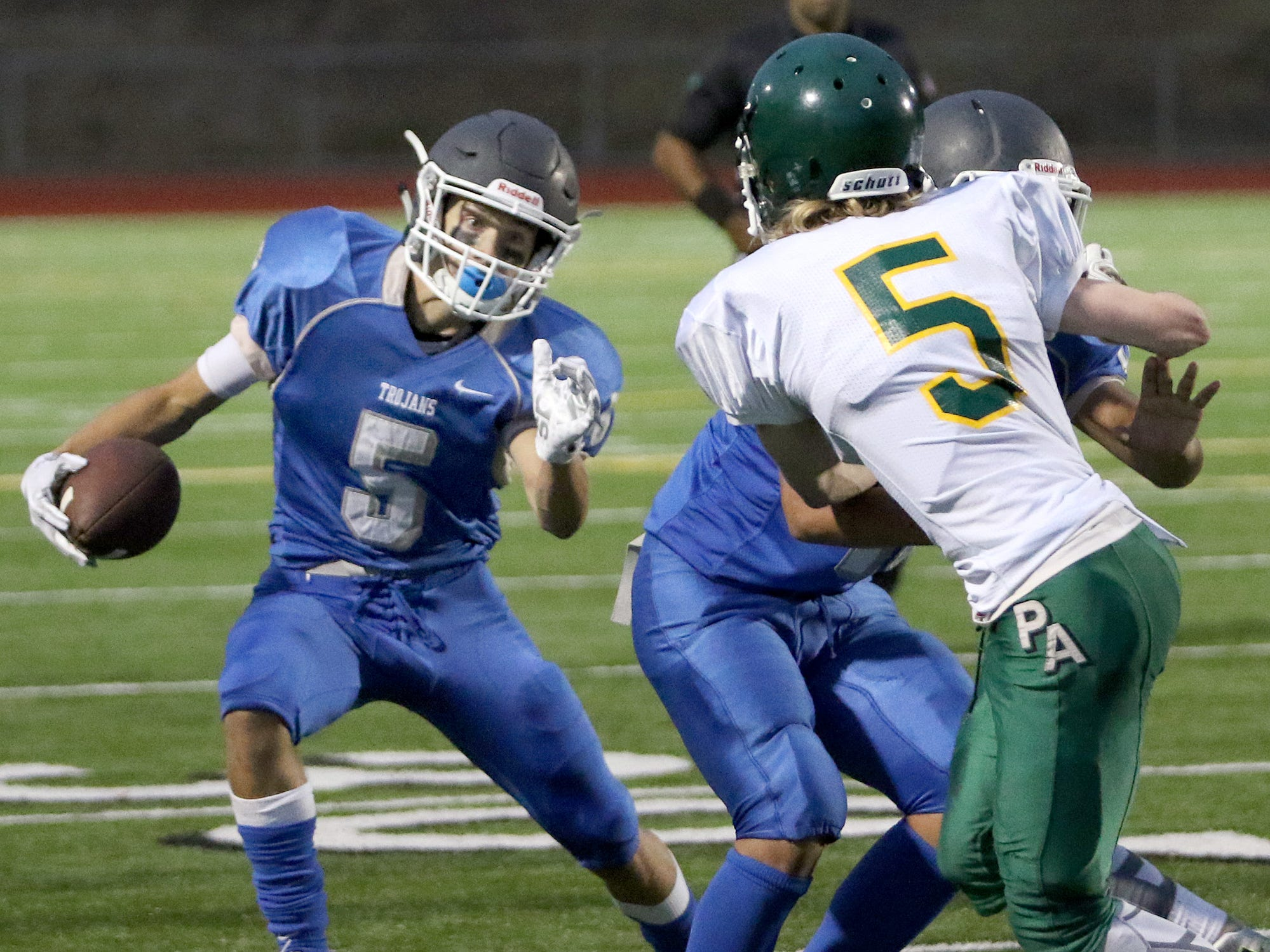 Olympic's Kaiden Rivers carries the ball for the Trojans' junior varsity team during Monday's game against Port Angeles. Olympic has a total of 55 players in its football program this season.