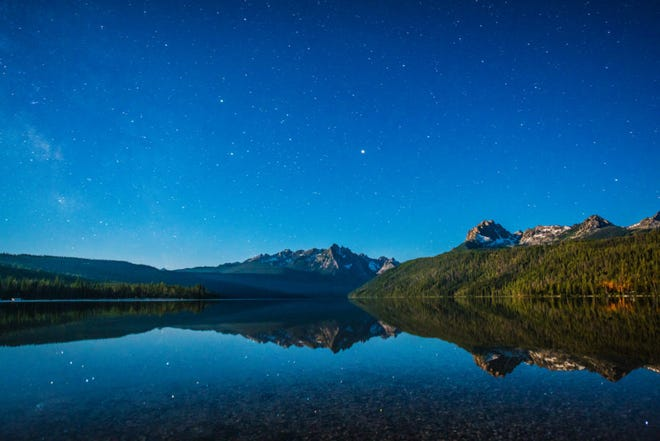 Redfish Lake in Stanley, Idaho, reflects the beauty of a starry night sky.