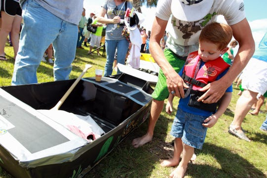 "Clyde Price (top) helps little brother Brennan Price, 4, put on his life jacket Saturday, Oct. 6, 2012 as they get ready to head out on their vessel, ""The Boat,"" during the cardboard boat race at Rockport Seafair."