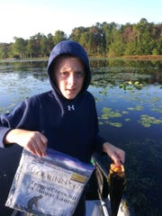 Dylan Lewis of Shamong holds the  largemouth bass that won him a prize in the Reel*Time USA Catch and Release  nationwide competition. Rylan is holding a Courier-Post newspaper as proof of the date that he caught the fish.