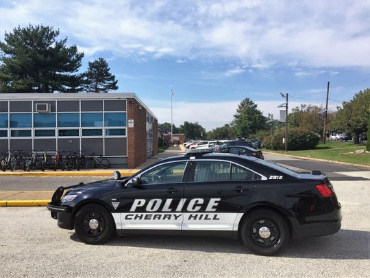 A police car sits outside Cherry Hill High School West during a lockdown prompted by a rumor about a gun on campus.