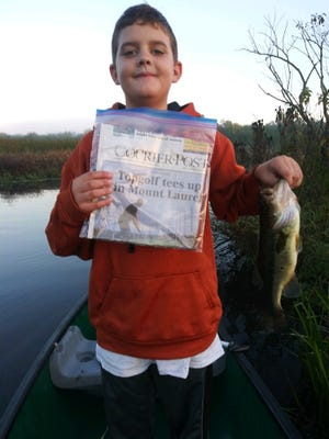 Rylan Gorin of Shamong holds the  largemouth bass that won him a prize in the Reel*Time USA Catch and Release  nationwide competition. Rylan is holding a Courier-Post newspaper as proof of the date that he caught the fish.