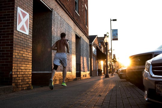 An afternoon runner passes by a boarded-up building, formerly owned by Integrated Services, that is currently marked with a red X on Water Street and may soon be planned for demolition.