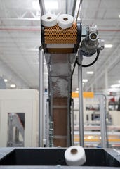 Rolls of toilet paper drop into an assembly line chute to be packaged and sold at the new $400 million Sofidel plant.
