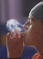 A young man smokes a marijuana cigarette.