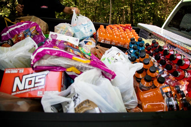 Volunteers bring donations of food and water for officers in the manhunt of Kirby Wallace Thursday, Oct. 4, 2018, in Woodlawn, Tenn.