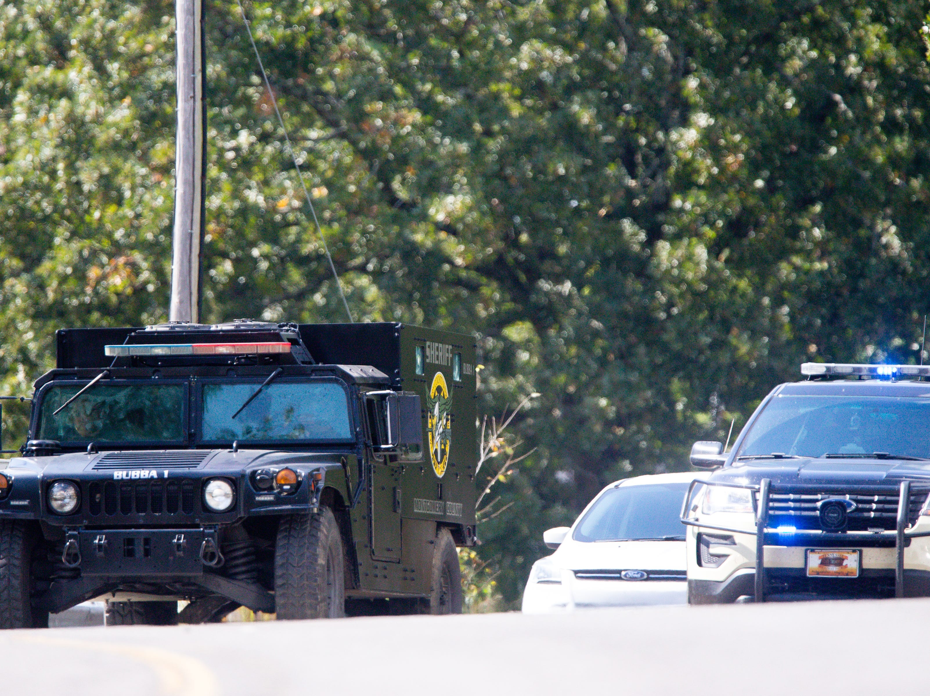 Montgomery County Sheriff's officers pass the checkpoint off of Poplar Springs Road during the manhunt of Kirby Wallace Thursday, Oct. 4, 2018, in Indian Mound, Tenn.
