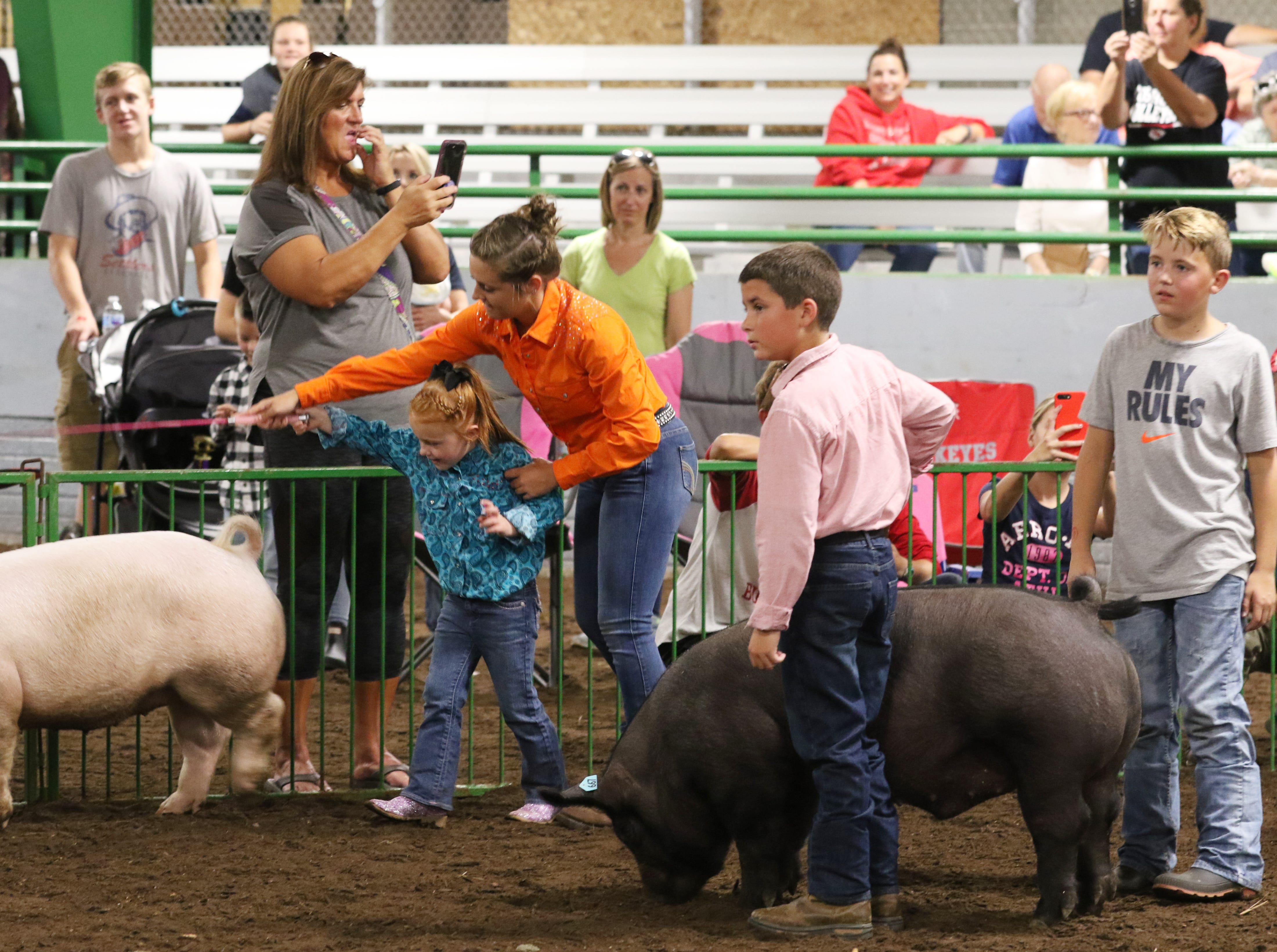 Youngsters take part in the swine show at the Coshocton County Fair on Wednesday.