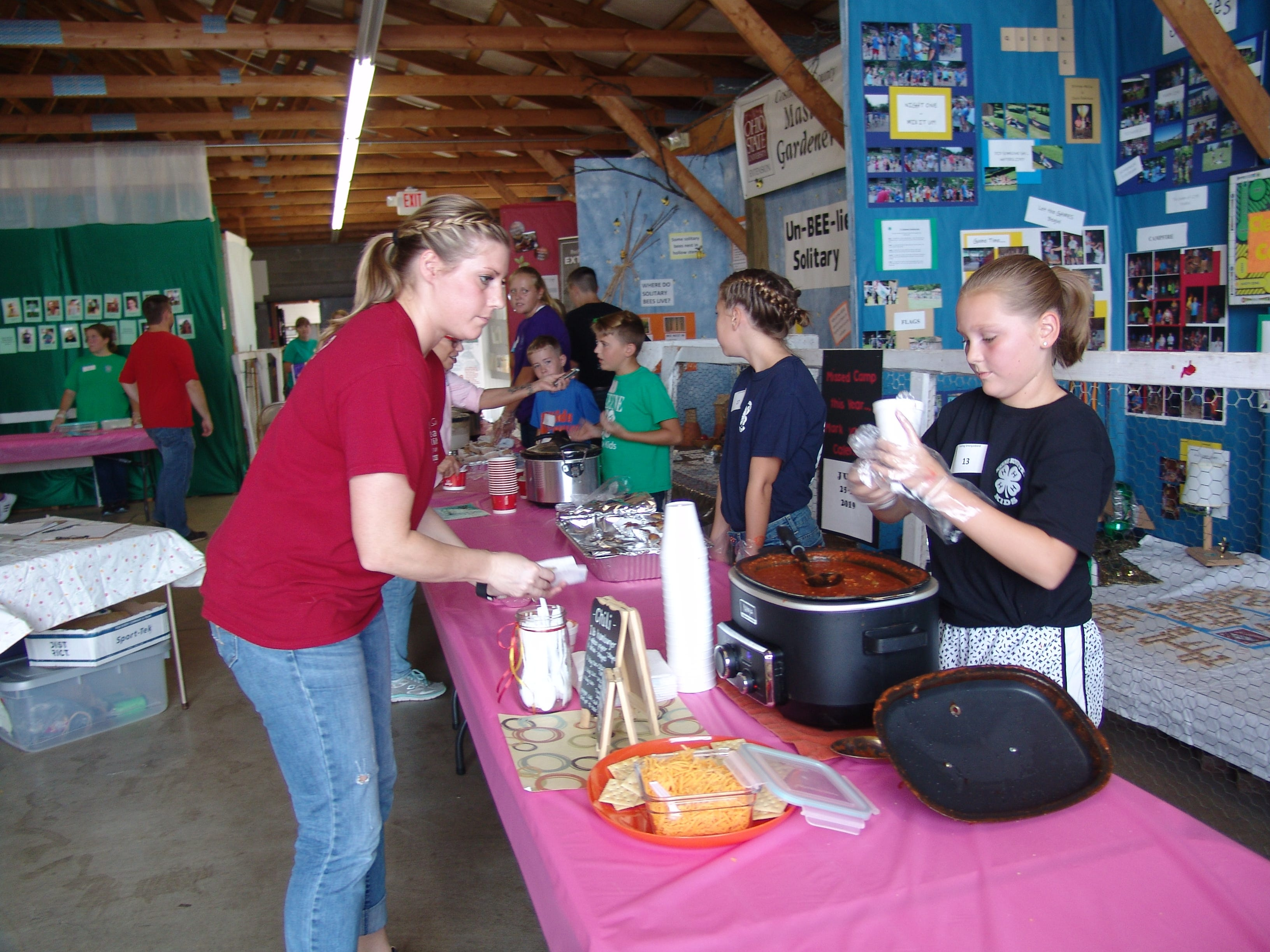 Katie Haumschild, Kamelid Kushers 4-H advisor and smorgasbord judge, receives chili from Madison Hammond.