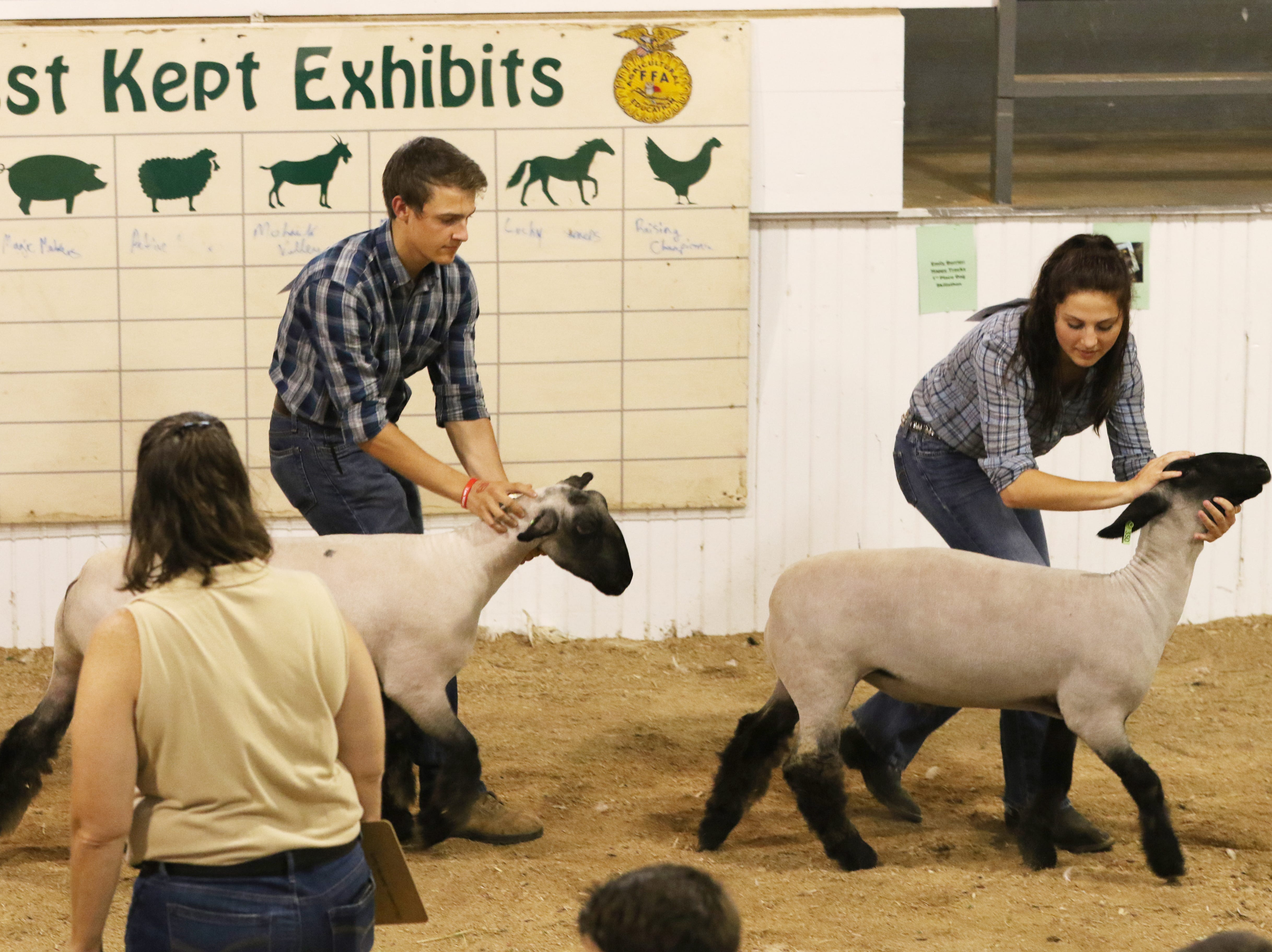 Kalie Rettos, right, and Ty Collins show lambs during the Showman of Showmen at the Coshocton County Fair on Wednesday.