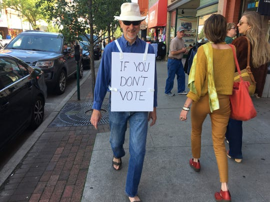 """Tom Boynton, 76, of Traverse City walks through downtown Traverse City wearing a lunchboard sign that reads on the front """"If You Don't Vote"""" and on the back """"You Don't Count."""" Boynton doesnt align with any particular party. """"I wear the sign because I am trying to get people to think,"""" said Boynton on Monday, Sept. 24, 2018."""