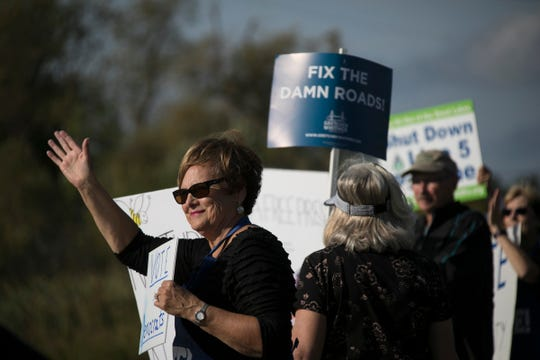 Donna Klinefelter of Kewadin joins a group of supporters of the Democratic Party as they stand along U.S. 31 in Elk Rapids on Monday, Sept. 24, 2018.