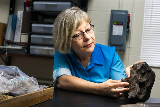 Professor Monaliza Sirbescu shows off a meteorite that's been in a Grand Rapids man's home for years.