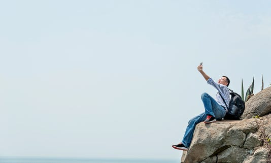 Man Using Mobile Phone By The Sea