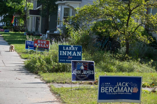 Democrat and Republican signs sit juxtaposed in yards in a Traverse City neighborhood on Monday, Sept. 24, 2018.