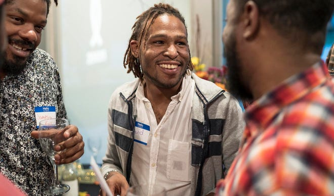 David Nelson, center, talks to Jamesion King, left, and Damon Percy, all of Detroit, during the Hotter Than July 2019 kickoff event at LGBT Detroit in Detroit, Tuesday, October 2, 2018.