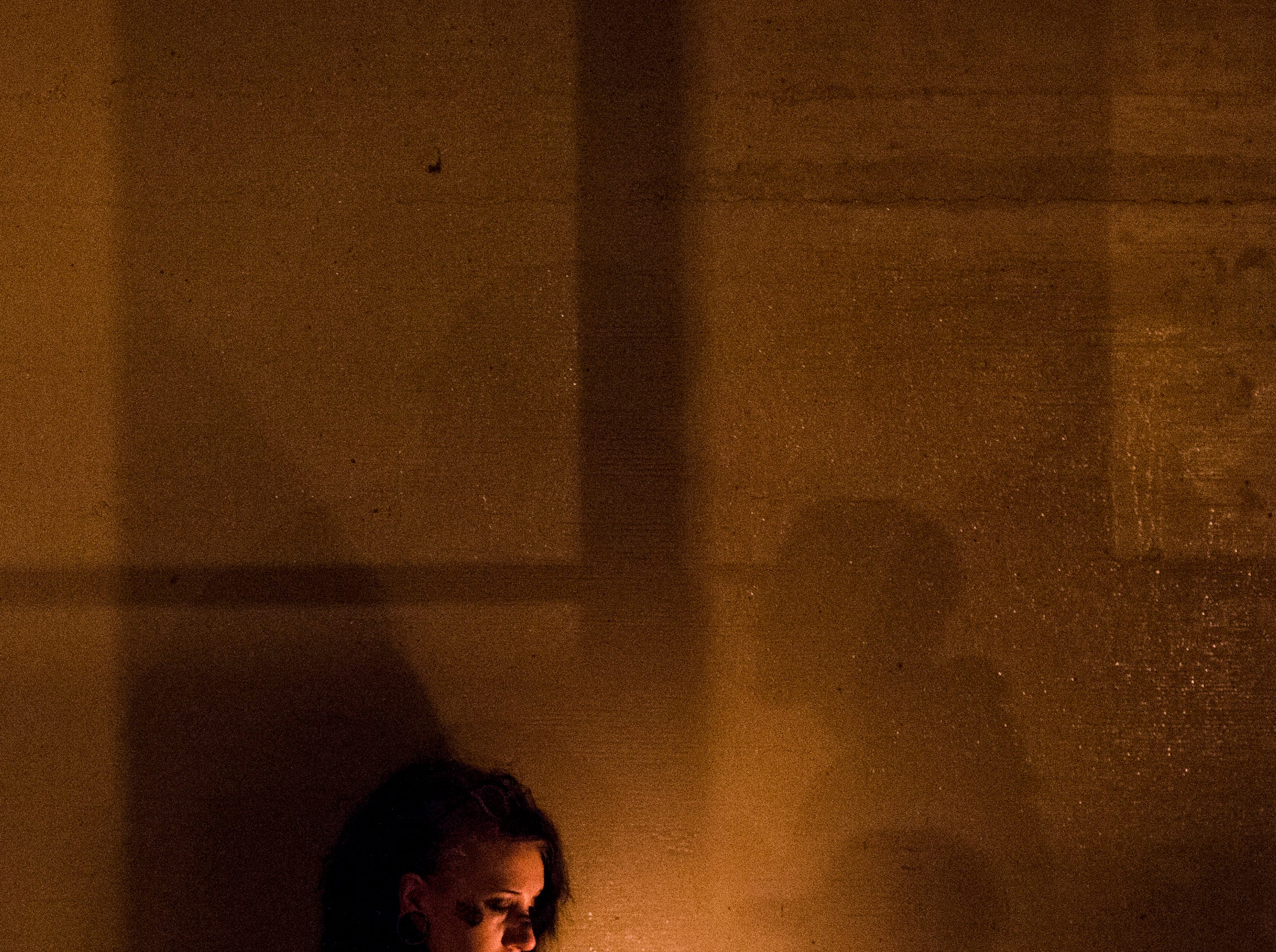 Waterford resident Shelby Isenbarg copes with the death of Anthony Comstock during a candlelight vigil at the site where his body was recovered from the Flint River at Riverbank Park Wednesday, Oct. 3, 2018, in downtown Flint, Mich. Comstock went missing in the river Monday night.