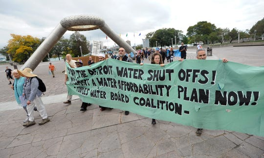 Members from various groups walk from Hart Plaza toward a press conference at the Spirit of Detroit Thursday as they carry a sign asking government officials to stop Detroit water shutoffs.