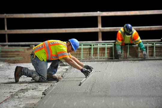 Road construction workers pour and spread wet concrete over a rebar mesh on the I-75 Rouge River Bridge downriver on June 25, 2018.