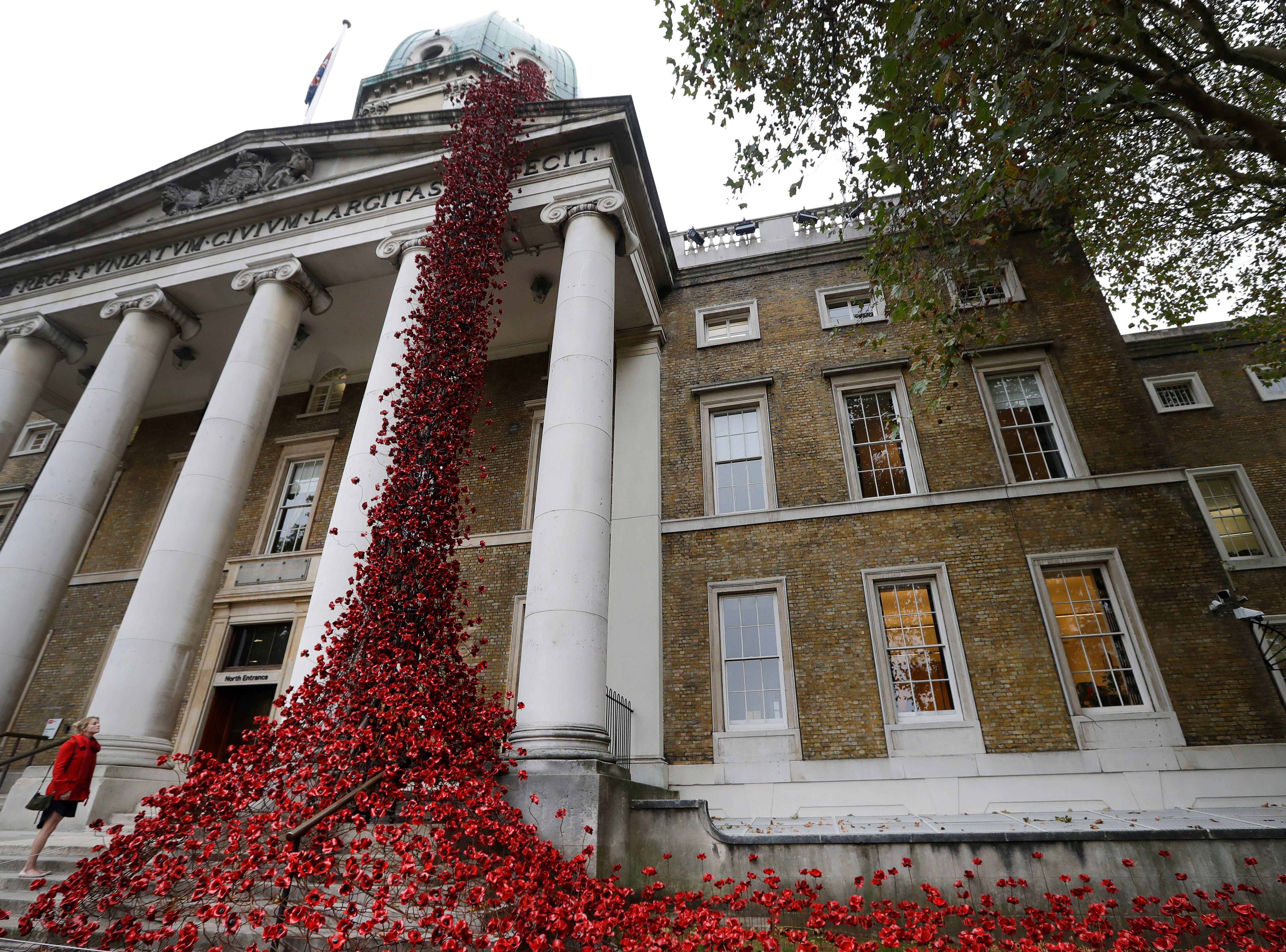 """A woman looks up toward the poppy sculpture """"Weeping Window,"""" by artist Paul Cummins and designer Tom Piper, at The Imperial War Museum in London, Thursday, Oct. 4, 2018."""