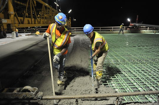 Road construction workers pour and spread wet concrete over a rebar mesh on theI-75 Rouge River Bridge downriver on June 25, 2018.