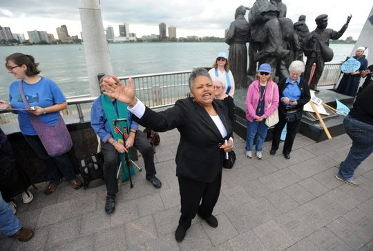 Monica Lewis-Patrick, a member of the People's Water Board, addresses the crowd during a prayer service held near the Detroit Riverwalk, Thursday.  A coalition of clergy and water rights activists are demanding an end to water shutoffs.