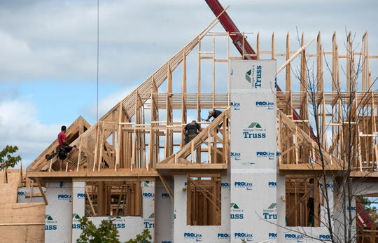 Construction workers build luxury houses at the David Campo Builders 'Casa Loma' development in Novi.