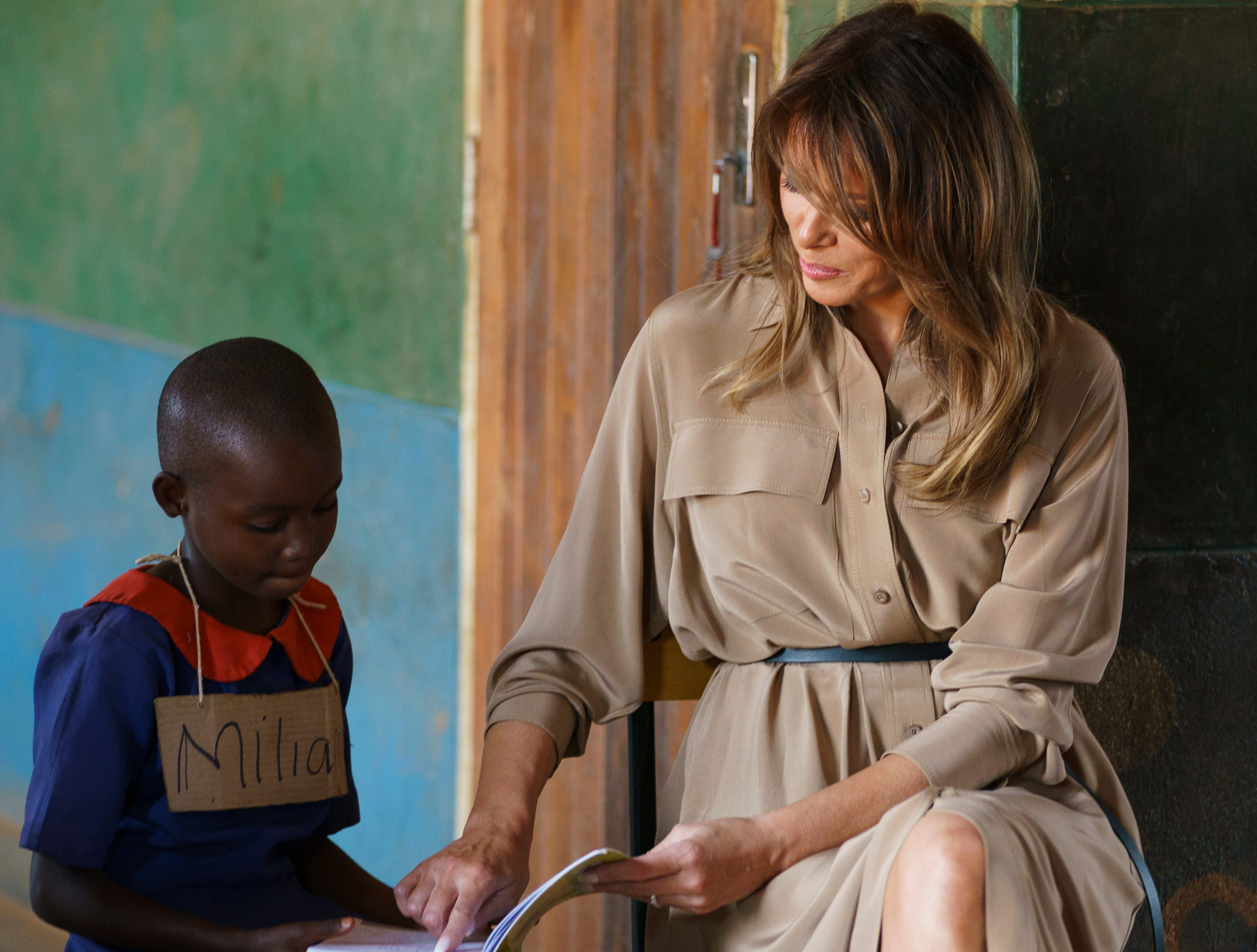 Melania Trump helps a student during the first lady's visit to a language class at Chipala Primary School, in Lilongwe, Malawi, Thursday, Oct. 4, 2018.