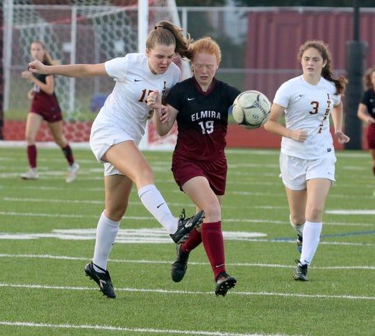 Mae Conuel of Ithaca, left, kicks the ball as Caylee Boorse of Elmira defends during girls soccer Oct. 3, 2018 at Ernie Davis Academy.