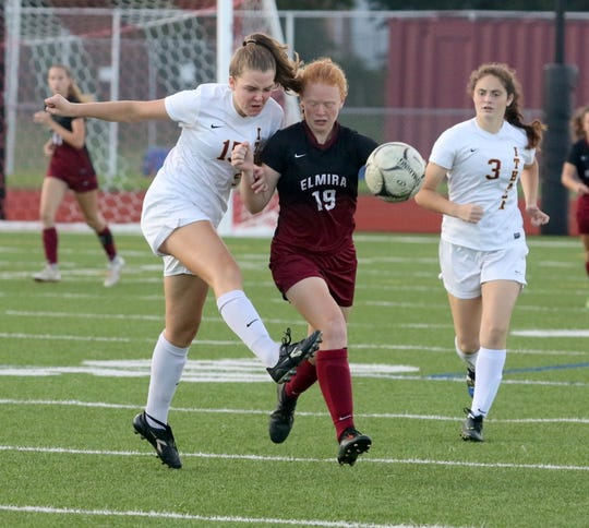 Mae Conuel of Ithaca, left, kicks the ball as Caylee Boorse of Elmira defends during girls soccer Oct. 3, 2018 at Ernie Davis Academy.