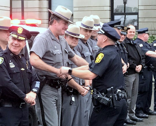 "Elmira police officer Jeremy Oakes greets other law enforcement officers who turned out Thursday for his ""walkout"" retirement ceremony."