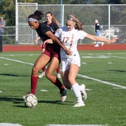 Zaria DeMember-Shazer, left, of Elmira battles Ithaca's Seneca Blakely-Armitage for possession during girls soccer Oct. 3, 2018 at Ernie Davis Academy.