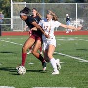Zaria DeMember-Shazer, left, of Elmira battles Ithaca's Seneca Blakely-Armitage for possession during girls soccer Oct. 3, 2018 at Ernie Davis Academy.