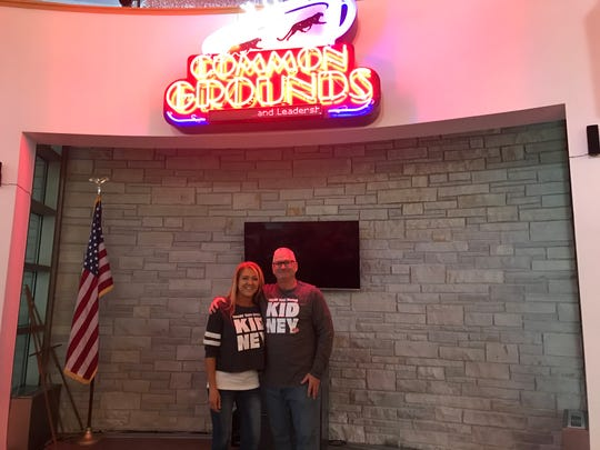 Nicole Braatz, left, and Paul Osterholm, right, met at Common Grounds in 2001 when she was commissioned to make the sign they stand below. He donated his kidney to her.