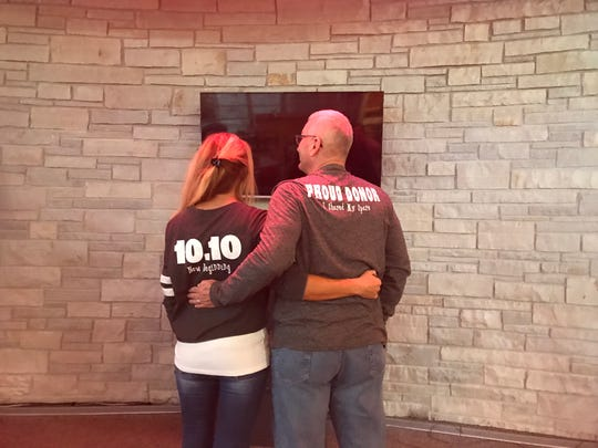 """Nicole Braatz, left, and Paul Osterholm, right, show off the shirts Braatz created, which read """"Share Your Spare Kidney"""" on the front."""