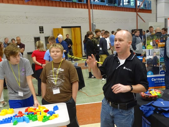 Kent Painter, a Style Crest project engineer, leads area high school students through a team building and problem solving exercise Thursday at the THINK Manufacturing Showcase at Terra State Community College.