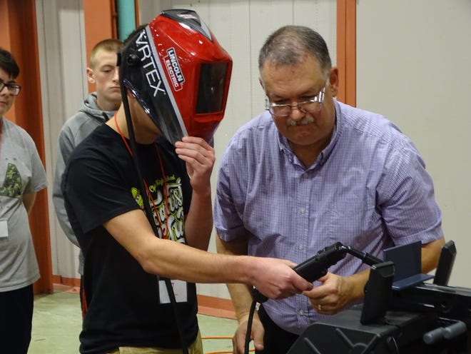 Stephen Bruno, an automation sales representative with OE Meyer Co., watches as Clyde High School freshman Gavin Gill dons a welder's mask and takes part in a welding simulation Thursday at the THINK Manufacturing Showcase at Terra State Community College.