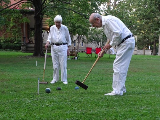 Alice Livingston, pictured right, looks on as her husband, Paul, hits a shot on the lawn Wednesday at the Rutherford B. Hayes Presidential Library & Museums. The Livingstons are members of the Hayes Croquet Club, which was formed in 2009.