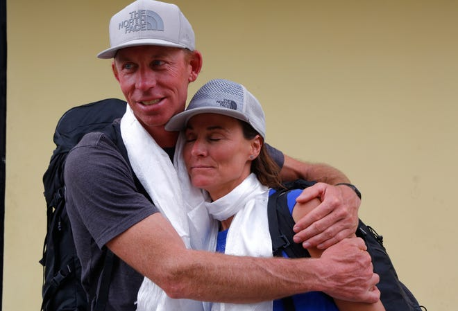 James Morrison of Tahoe, California, hugs Hilaree Nelson of Telluride, Colorado, as the pair arrived in Kathmandu, Nepal, Thursday, Oct. 4, 2018. The two American extreme skiers who overcame weather conditions, delays, equipment and oxygen issues to successfully ski down from the summit of the world's fourth-highest peak Mount Lhotse returned safely from the mountains. (AP Photo/Niranjan Shrestha)