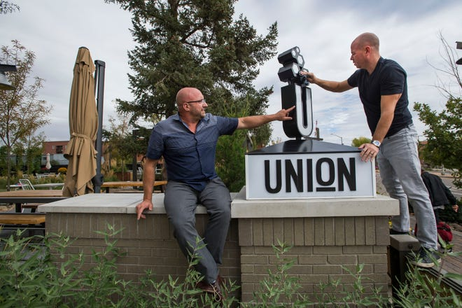Old Town Restaurant Group co-owners Ryan Houdek, left, and Ty Fulcher clean up one of their restaurant's signs before a portrait on Thursday, Oct. 4, 2018, at Union bar & soda fountain in Old Town Fort Collins, Colo.