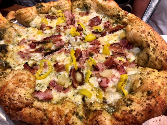 The Maui Wowie pizza from Mellow Mushroom features jerk chicken, ham, bacon, pineapple and banana peppers with a pesto-sauce base. The pie is unique to the new south Fort Myers store.